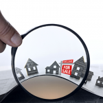 Hand holding magnifying glass showing vector houses with a for sale sign out front
