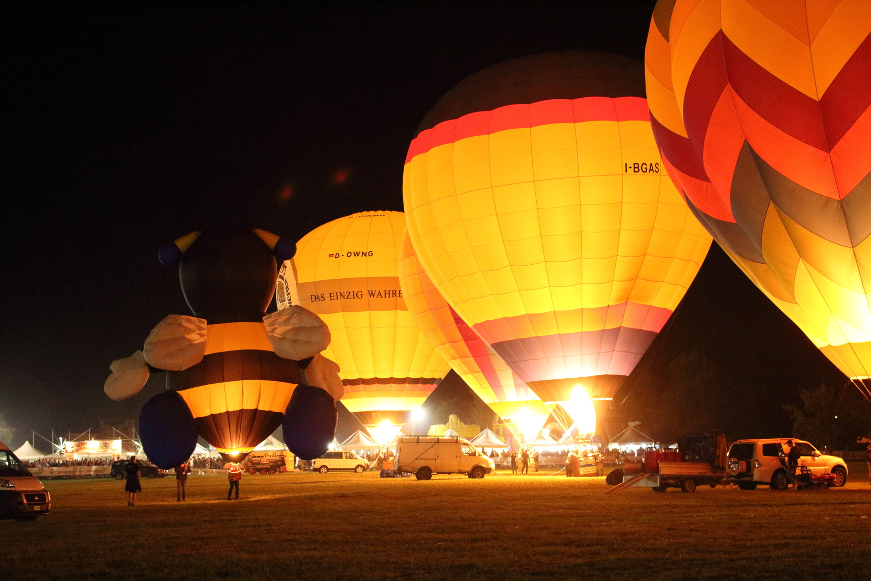 Four hot air balloons lit up at night